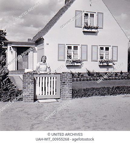 Ein Mädchen steht am GArtenzaun ihres Elternhauses., Sammlung Wittmann