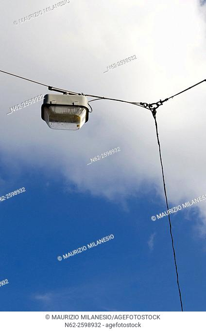 streetlight connected to cords in front of a blue sky and white clouds