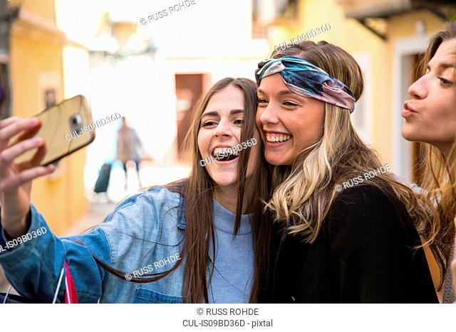 Friends taking selfie in street