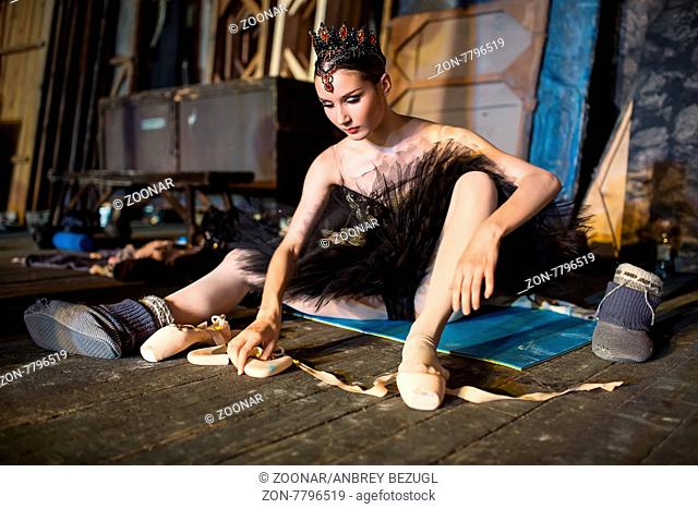 Prima ballerina sitting on the warm-up backstage before going on stage for a solo program on the stage in a performance of Swan Lake, view the profile