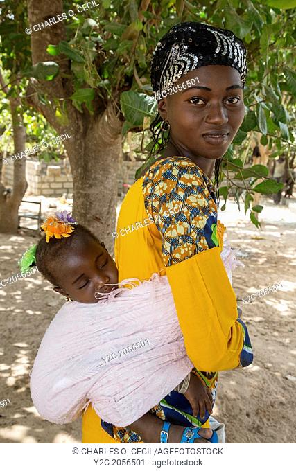 Young Gambian Mother Carrying Sleeping Daughter on Back, Fass Njaga Choi, North Bank Region, The Gambia