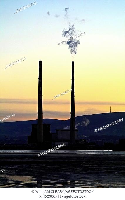 Poolbeg power station, Dublin, in the evening light, smoke billowing from the right cooling tower. Ireland