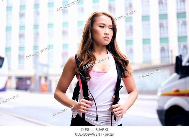Young woman carrying backpack waiting on city street