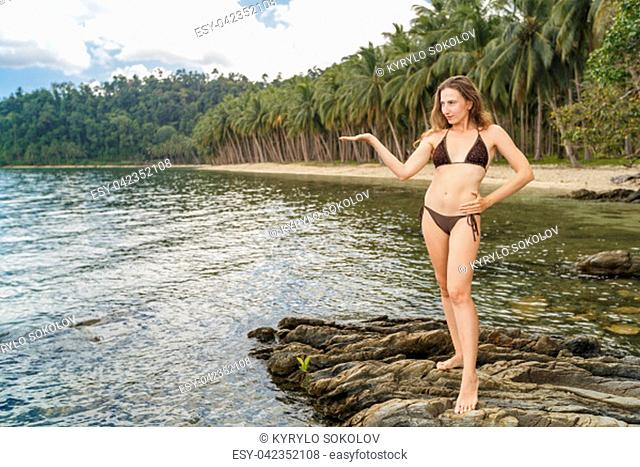 Young woman on the rock. Happy island lifestyle. Palm tree and crystal sea of tropical beach. Vacation at Paradise. Sea beach relax, travel to Palawan island