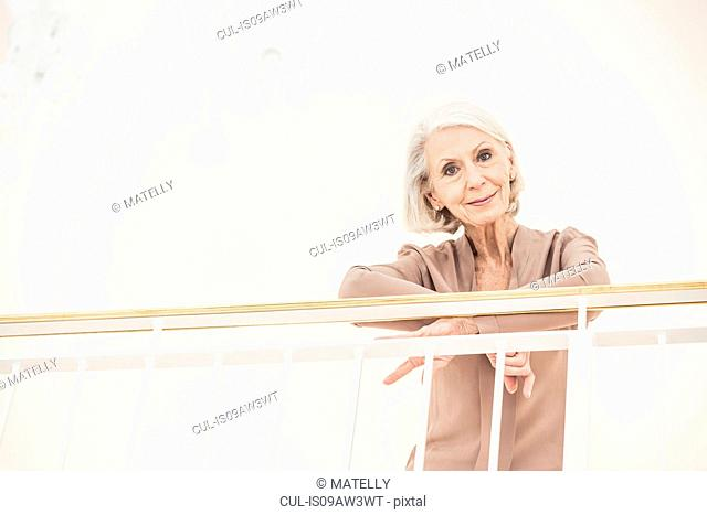 Portrait of senior woman at home, leaning against banister