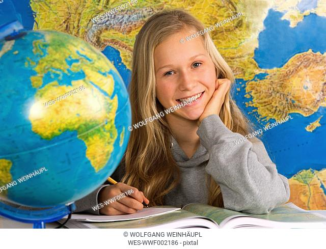 Teenage girl writing on book with globe, smiling, portrait