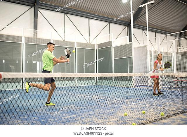 Two paddle tennis players on court playing a match