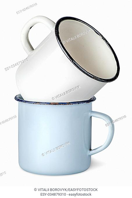 Two old enameled mugs on each other isolated on white background