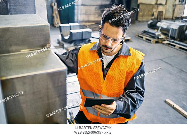 Man with tablet wearing protective workwear working in factory