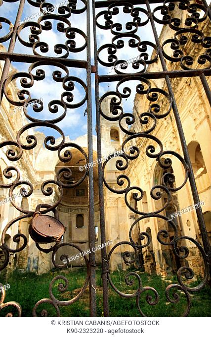 Ruin of the earthquake stricken church of Bussana Vecchia seen through an old, rosty metal gate, Liguria, Italy, Europe
