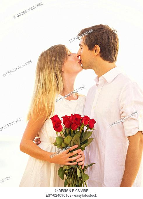 Young Couple in Love, Man giving beautiful woman bouquet of red roses, Romantic Date
