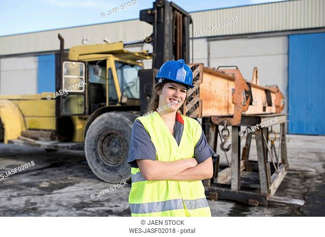 Portrait of confident female worker on industrial site near bulldozer