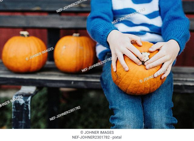 Boy sitting on bench and holding pumpkin