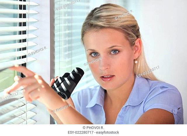 Woman peering through blinds with binoculars