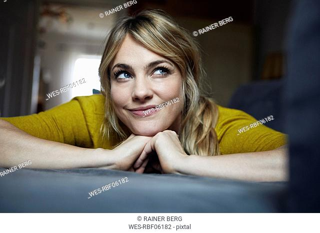 Portrait of woman lying on the couch at home thinking