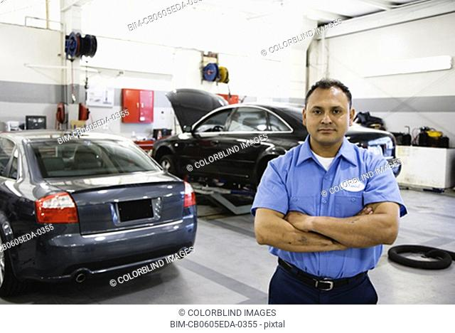 Hispanic male auto mechanic standing in auto repair shop