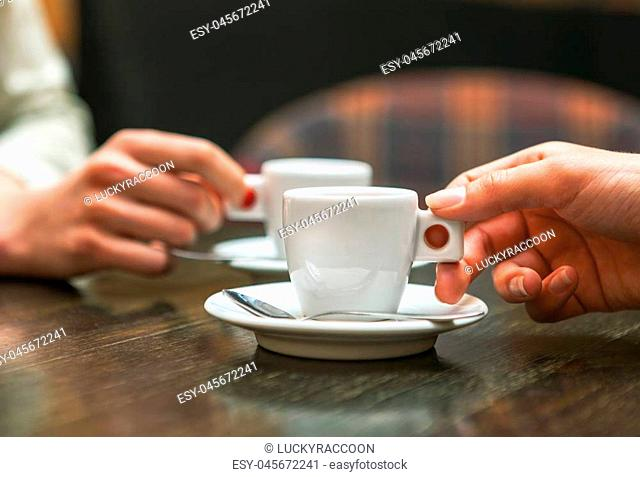 Closeup of two people holding cups of coffee sitting in cafeteria