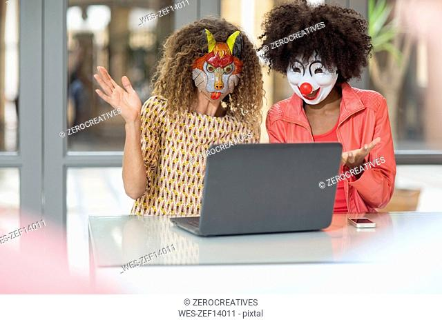 Two women in office wearing masks sharing laptop