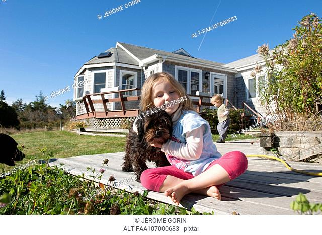 Little girl sitting on deck with pet dog