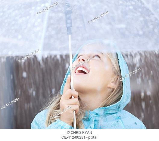Close up of girl under umbrella looking up at downpour