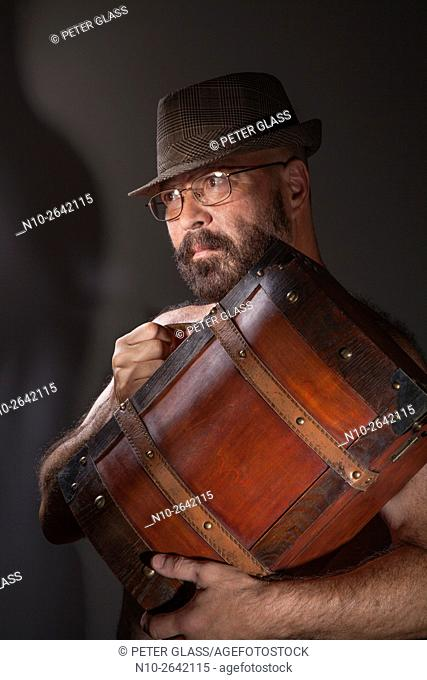 Middle age man with glasses, hat, and no shirt. holding a wooden case