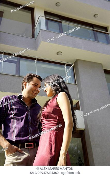 young couple outside apartment looking at each other