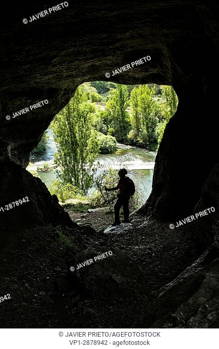 A walker stopped in the natural tunnel of access to the top of the canyon of La Horadada, with the river Pisuerga in the background