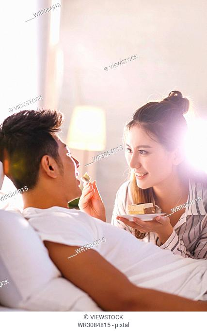 Young lovers eat cake