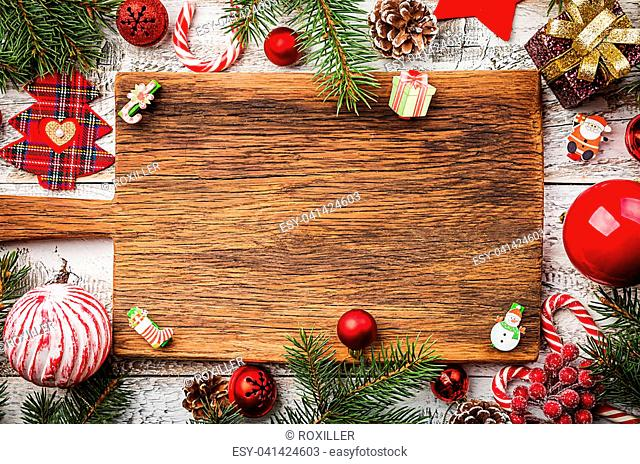 Christmas composition with fir tree branches and red christmas decorations on white wooden background, top view with copy space