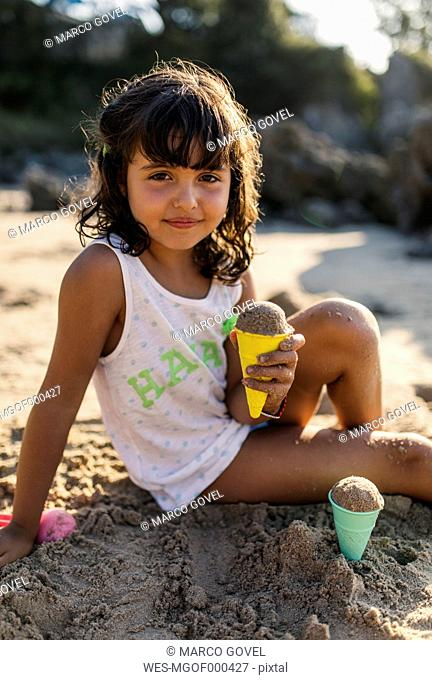 Spain, Llanes, portrait of little girl playing with sand on the beach
