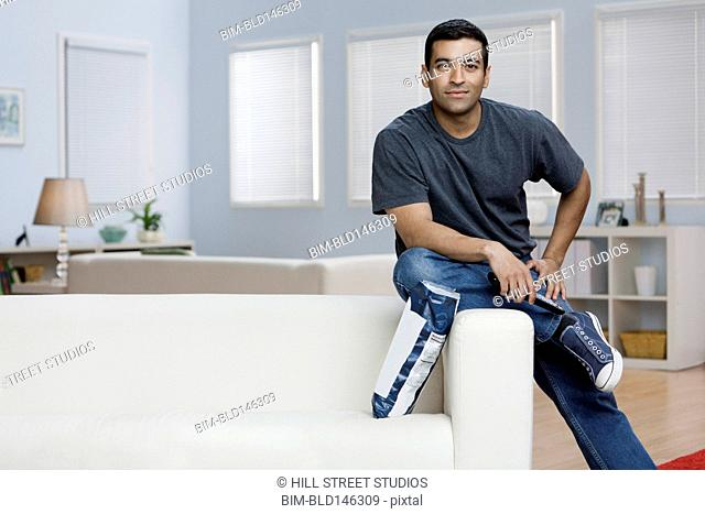 Hispanic man eating potato chips and watching television