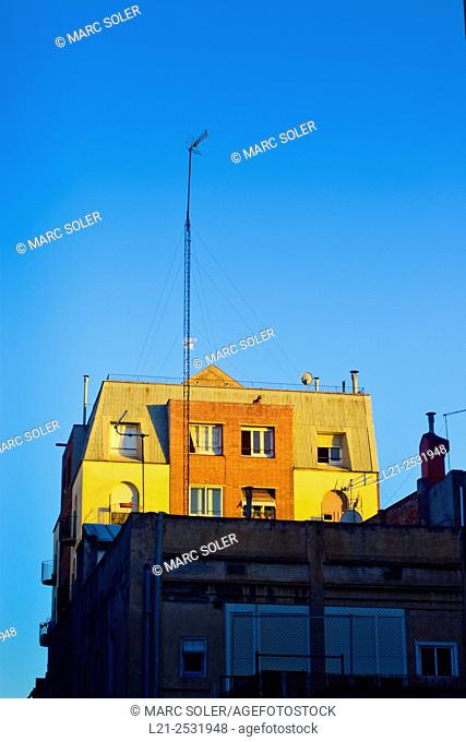 Long antenna and building, blue sky. Barcelona, Catalonia, Spain