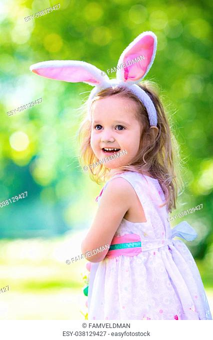 Little girl having fun on Easter egg hunt. Kids in bunny ears and rabbit costume. Children with colorful eggs in a basket. Toddler kid playing outdoor