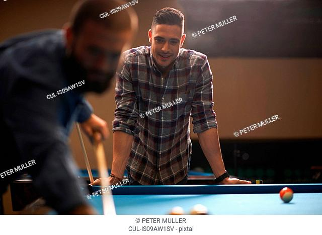 Man playing pool, friend in background