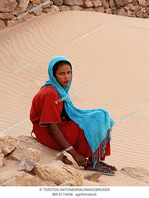 Young woman in colourful clothes sitting on stone, oasis of Al-Ghazali, Sudan
