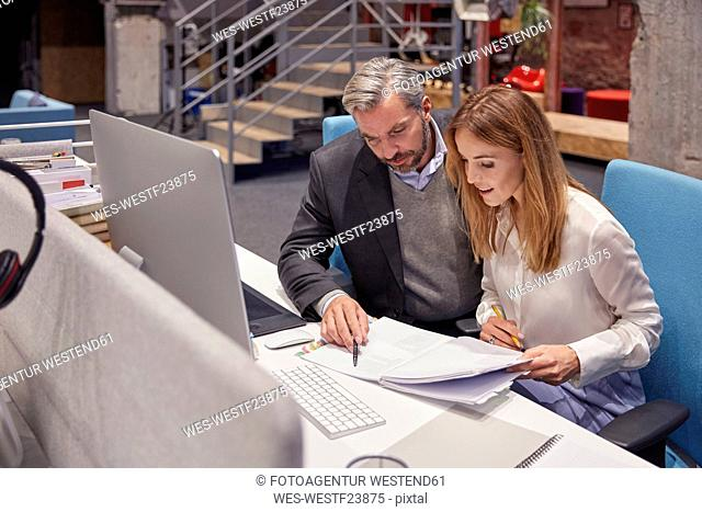 Businessman and woman working together in modern office