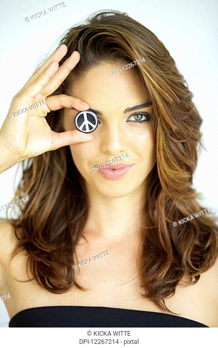 Young woman holding peace symbol in front of one eye; Kauai, Hawaii, United States of America