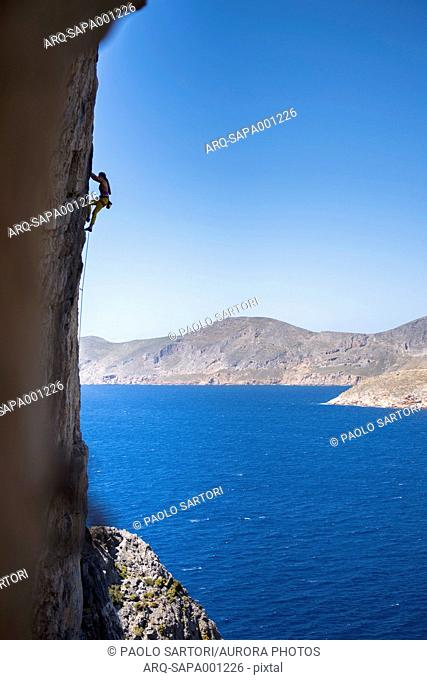 Woman climbing steep cliff in scenery with sea and coastline, Kalymnos, Greece