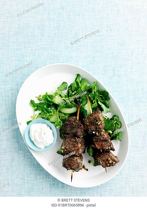 Plate of beef kebabs with salad