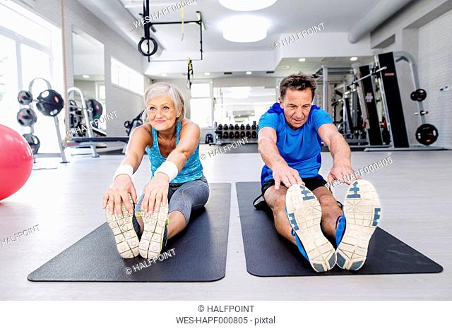 Senior man and mature woman exercising in fitness gym