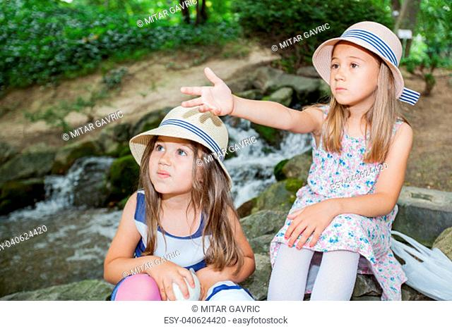 Portrait of cute little girls in elegant dress at park, spring day in nature