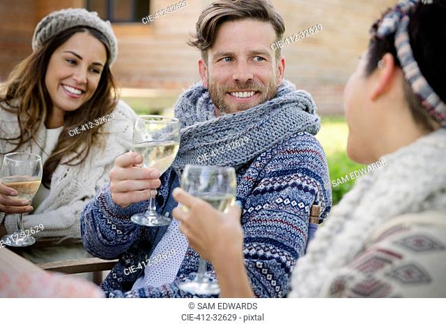 Smiling friends drinking wine on patio