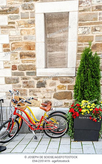 2 bicycles next to a wall and a plant container in Quebec City, Canada