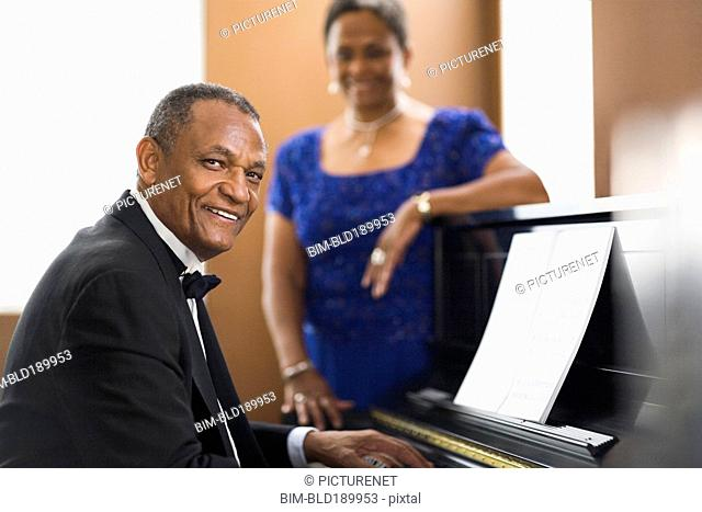 African woman watching african man play piano