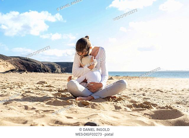 Mother cuddling with little daughter on the beach