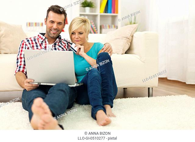Couple sitting on carpet at home and doing shopping online. Debica, Poland