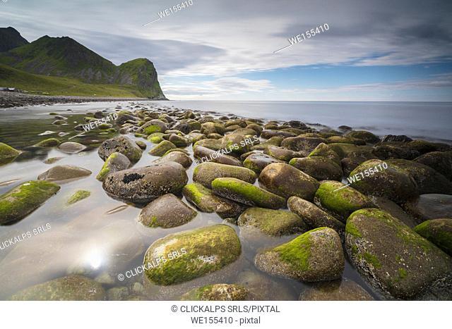 Rocks on the beach frame the calm clear sea Unstad Vestvagøy Lofoten Islands Norway Europe