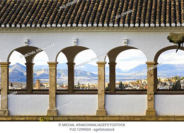Detail of palace in Generalife, Alhambra with panorama of Granada behind columns