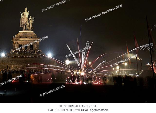 01 January 2019, Rhineland-Palatinate, Koblenz: New Year's Eve fireworks illuminate the sky above the equestrian statue of Emperor Wilhelm at the German Corner...