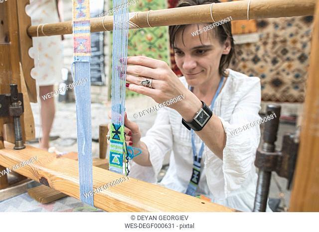 Woman weaving carpet with weaving loom